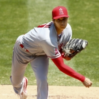 Angels two-way player Shohei Ohtani pitches against the Athletics on July 26 in Oakland. He surrendered five runs without an out in his first appearance on the mound in two seasons. | GETTY / VIA KYODO