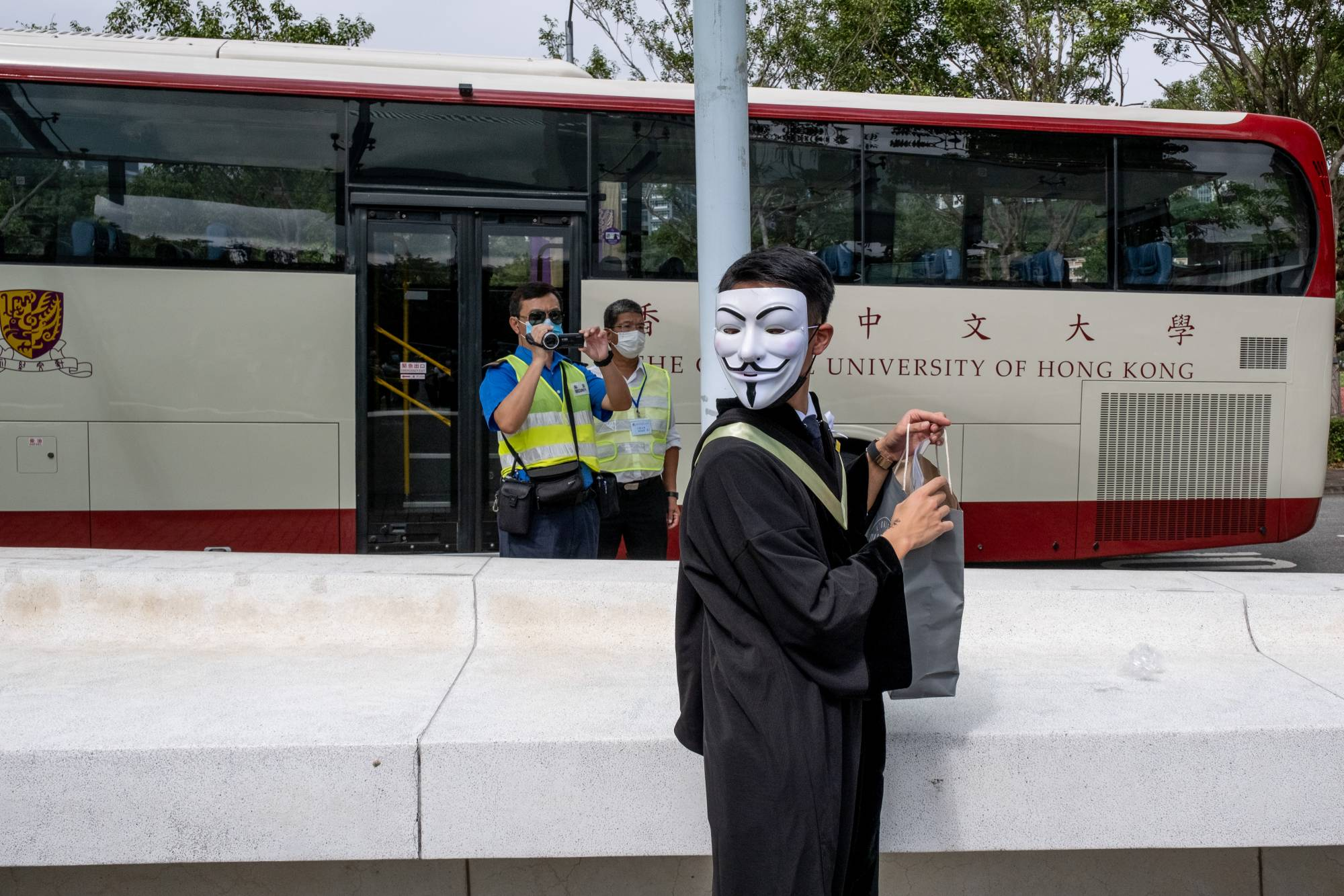 A graduating student wearing a Guy Fawkes mask attends a protest at the Chinese University of Hong Kong as a campus security officer observes with a video recorder on Thursday. | BLOOMBERG