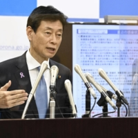 Yasutoshi Nishimura, the minister leading the government's COVID-19 response, speaks to the press in Tokyo on Nov. 12. | KYODO