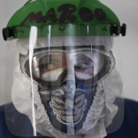 A health care worker wears a protective face mask designed with a Mexican wrestler motif in a ward designated for COVID-19 patients at the Ajusco Medio General Hospital in Mexico City on Thursday. | AP