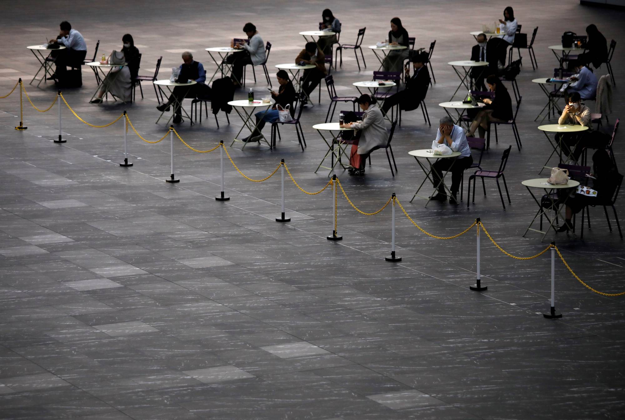People practice social distancing as they take a lunch break in Tokyo on Thursday. | REUTERS