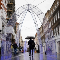 People walk in the rain past Christmas decorations in central London on Friday as life under a second lockdown continues in England. According to a new study by the Oxford University, individuals infected with coronavirus are unlikely to catch the illness again for at least six months. | AFP-JIJI