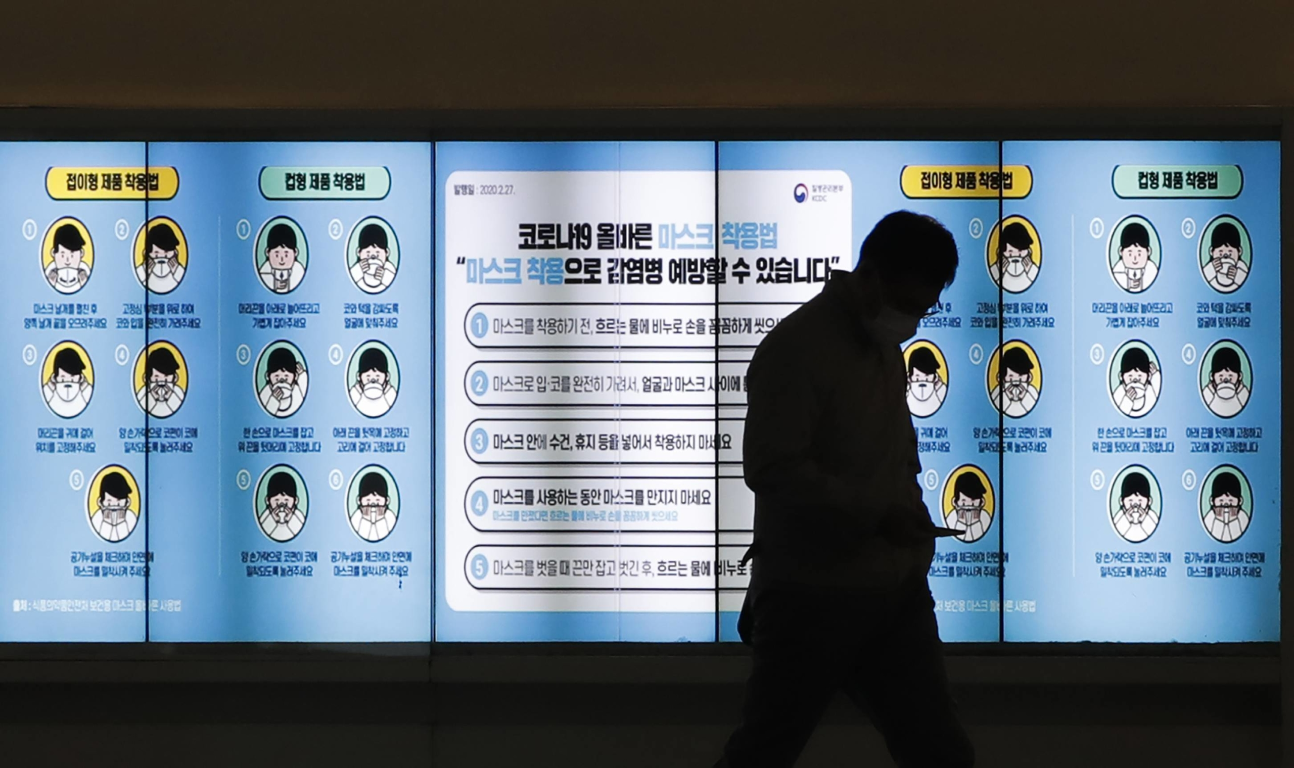 A man wearing a face mask walks past in front of a screen showing precautions against the coronavirus in Seoul on Friday. The letters read: 'How to wear a mask.'  | AP