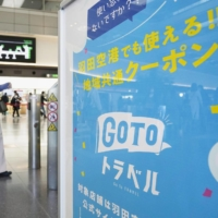 An advertisement for the Go To Travel campaign at Haneda Airport in Tokyo. Moving forward, Prime Minister Yoshihide Suga said prefectural governors will decide whether the travel campaign should be suspended in their respective areas. | KYODO