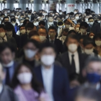 A station passageway is crowded with commuters wearing face masks to help curb the spread of the coronavirus during rush hour in Tokyo on Friday. | AP