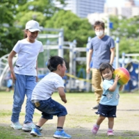 Children play at a park in Tokyo in May.  | KYODO