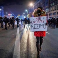 A demonstrator holds a placard next to police officers during a pro-choice protest in the streets of central Warsaw earlier this month.  | AFP-JIJI