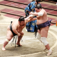 Ozeki Takakeisho (left) pushes out komusubi Terunofuji to win the championship playoff and clinch the top-division title at the November Basho. | NIKKAN SPORTS