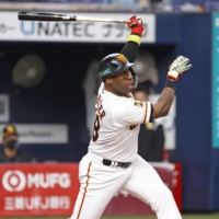 The Giants' Zelous Wheeler hits a solo home run during the fifth inning in Osaka on Sunday. | KYODO