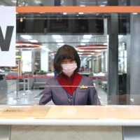 A flight attendant is seen behind a plastic shield amid the coronavirus pandemic at Songshan Airport in Taipei on Thursday.  | REUTERS