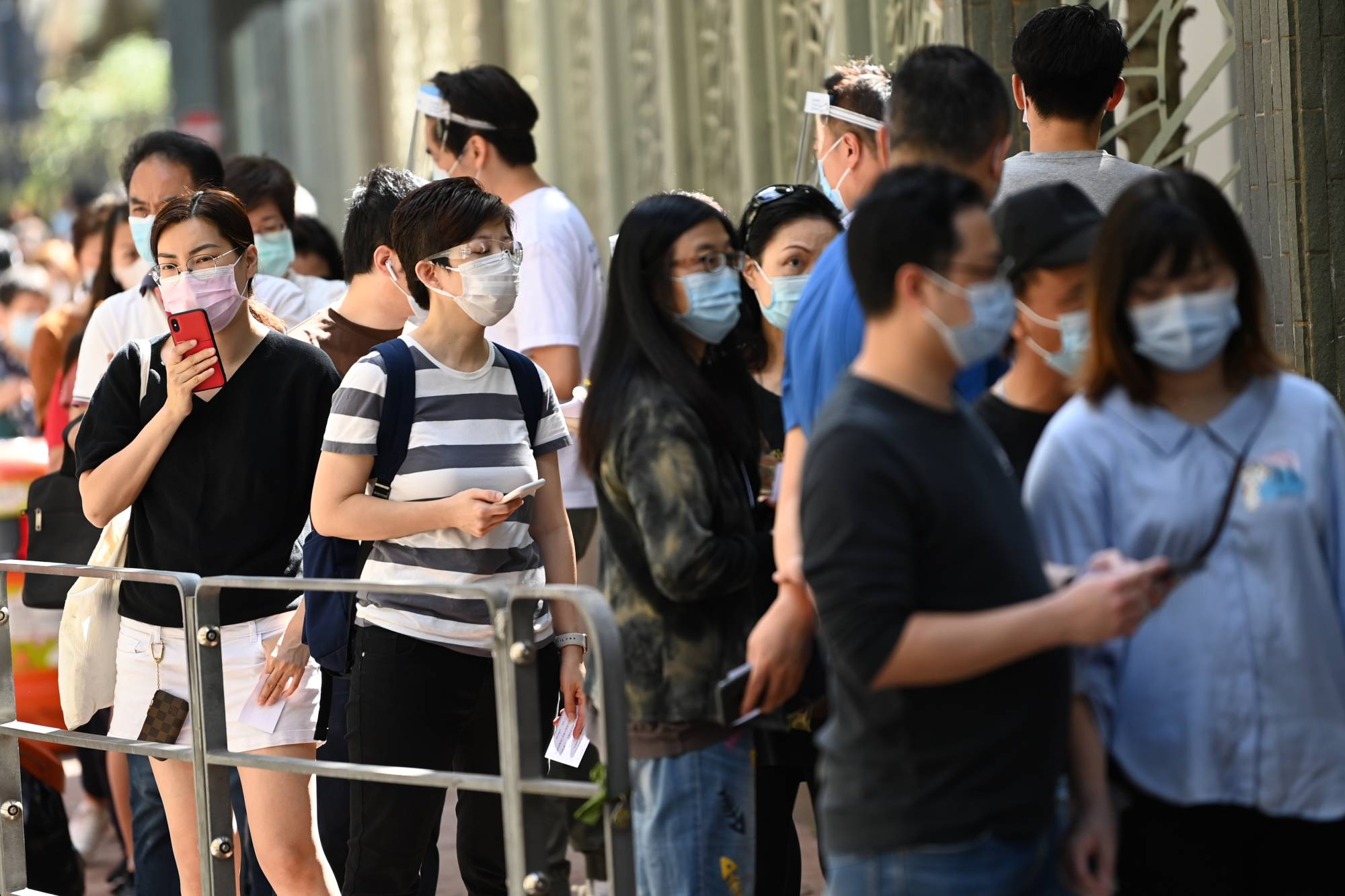 People line up outside a COVID-19 testing center in Hong Kong on Sunday.  | AFP-JIJI