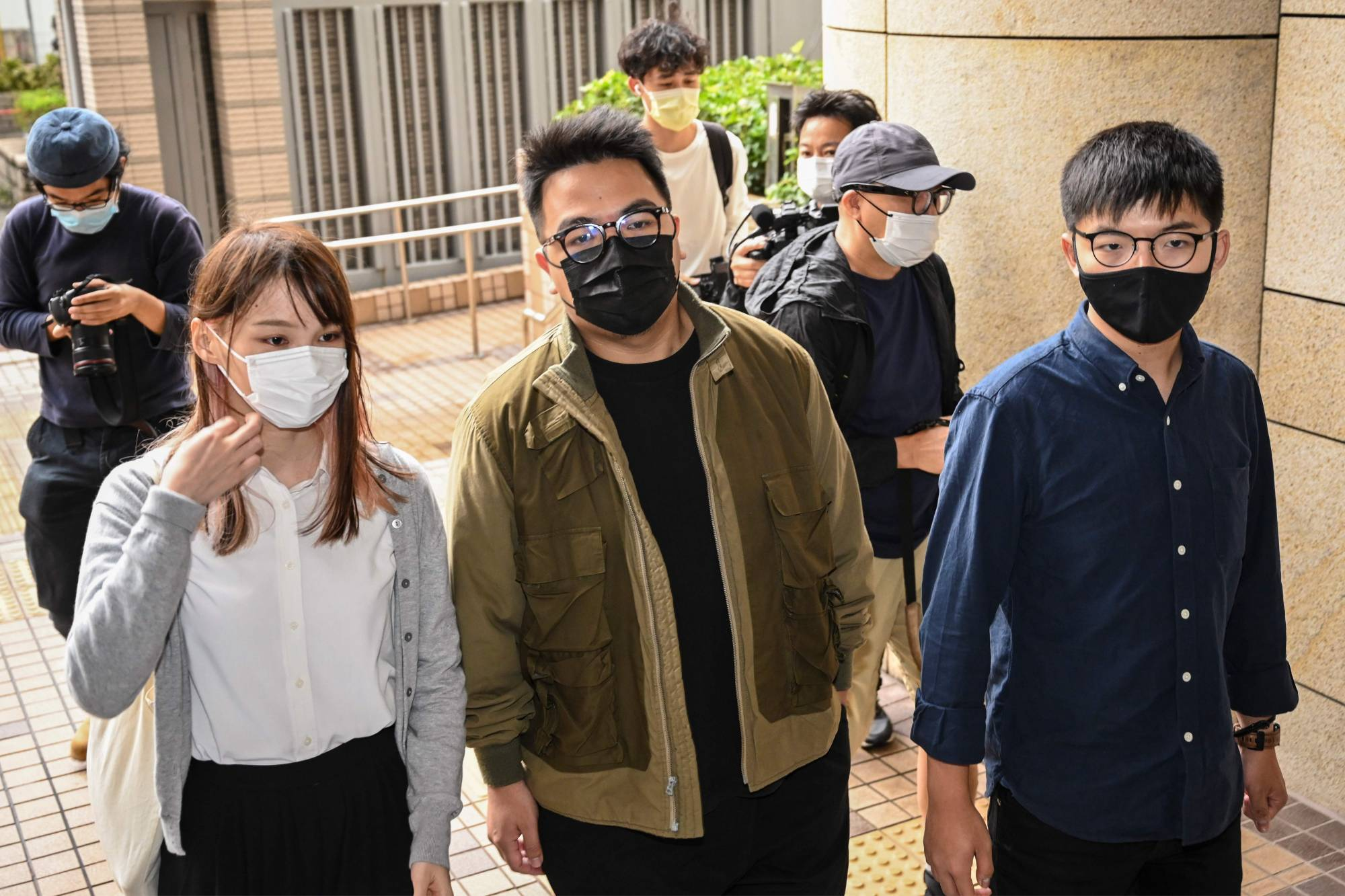 From left: Pro-democracy activists Agnes Chow, Ivan Lam and Joshua Wong arrive for their trial at West Kowloon Magistrates Court in Hong Kong on Monday.  | AFP-JIJI