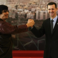 Syrian President Bashar al-Assad (right) shakes hands with Libya's leader Moamer Kadhafi at the opening session of the Arab Summit in Damascus in March 2008.  | AFP-JIJI