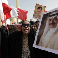 A pro-government protester shouts slogans as she holds a poster of Bahraini Prime Minister Khalifa bin Salman Al Khalifa during a march in Manama in February 2011.  | AP