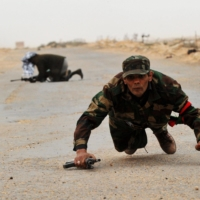 Libyan rebel fighters run for cover as shells explode nearby, a few kilometers from Bin Jawad, in March 2011.  | AFP-JIJI