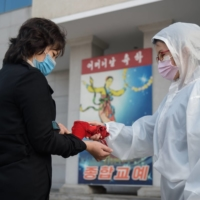 An audience member undergoes a novel coronavirus check as part of preventative measures against COVID-19 before a performance by North Korea's National Acrobatic Troupe at the Pyongyang Circus Theater on Nov. 16. | AFP-JIJI