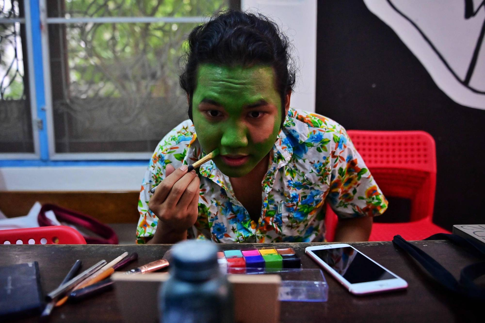 Pro-democracy activist, performing arts student and aspiring drag queen Siraphob 'Raptor' Attohi transforms himself into Elphaba from the hit musical 'Wicked' before a gay pride parade in Bangkok earlier this month. | AFP-JIJI