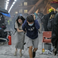 Protesters run for cover after riot police fired tear gas as they tried to escape from the Hong Kong Polytechnic University campus and police in November last year.  | AFP-JIJI