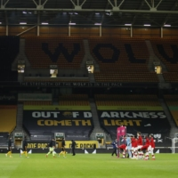 Players and officials line up between Monday's Premier League match between Wolverhampton and Southampton in Wolverhampton, England. Premier League teams in some regions will be able to admit limited numbers of fans from Dec. 2. | POOL / VIA REUTERS