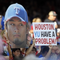 Fans hold signs supporting Rangers starting pitcher Yu Darvish before a game against the Astros in Arlington, Texas, on June 15, 2012. | REUTERS