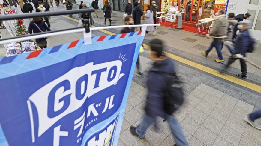 A sign for the Go To Travel campaign hangs on a shopping street in Sapporo. The government announced Tuesday Sapporo and Osaka will be temporarily removed from the campaign.