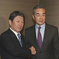 Toshimitsu Motegi (right), foreign minister, shakes hands with Wang Yi, his Chinese counterpart, in Munchen, Germany, in February. | COURTESY OF JAPAN'S FOREIGN MINISTRY VIA KYODO