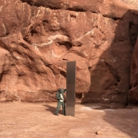 A worker inspects a metal monolith that was found installed in the ground in a remote area of red rock in Utah on Nov. 18.  | UTAH DEPARTMENT OF PUBLIC SAFETY / VIA AP
