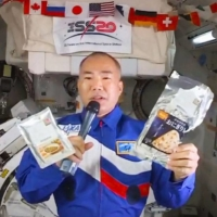 Japanese astronaut Soichi Noguchi holds space food items he brought from Japan to the International Space Station. | KYODO