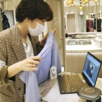 A sales clerk at the Isetan Mitsukoshi Holdings Ltd. department store in Shinjuku Ward, Tokyo, conducts a demonstration Wednesday of an app that enables customers to chat via videoconference with sales clerks and see products in the store. | KYODO