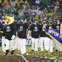 The Hawks carry the championship banner as they parade around the field after winning the Japan Series on Wednesday. | KYODO