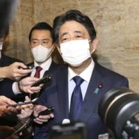 Former Prime Minister Shinzo Abe is surrounded by reporters in the Diet on Tuesday. | KYODO