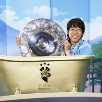 Frontale veteran Kengo Nakamura poses with the J. League schale in a gold bathtub on Wednesday in Kawasaki. | KYODO