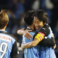 Kawasaki veteran Kengo Nakamura (right) embraces teammate Yu Kobayashi at full time on Wednesday at Todoroki Stadium. | KYODO
