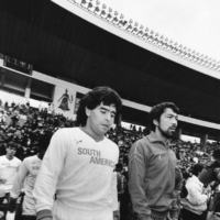 Diego Maradona (left) enters the pitch alongside Yasuhito Okudera before the 1987 Xerox Super Soccer friendly between a South America XI and a Japan Soccer League XI on Jan. 27, 1987, in Tokyo. | YOKOHAMA FC / VIA KYODO