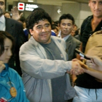 Diego Maradona shakes hands with fans after arriving at Narita Airport to attend the 2002 FIFA World Cup final in Yokohama on June 28, 2002. | REUTERS