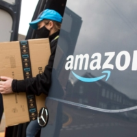An Amazon.com Inc. delivery driver carries a customer order from the back of a delivery van in Westcliff-on-Sea, U.K., on Thursday. | BLOOMBERG