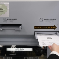 Tellers at Sumitomo Mitsui Bank's Chuorinkan branch in Yamato, Kanagawa Prefecture, will no longer handle cash directly and will use QR codes instead. | KAZUAKI NAGATA