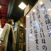 A notice of shortened hours is posted at the entrance of a restaurant in Minami district, Osaka, on Thursday. | KYODO