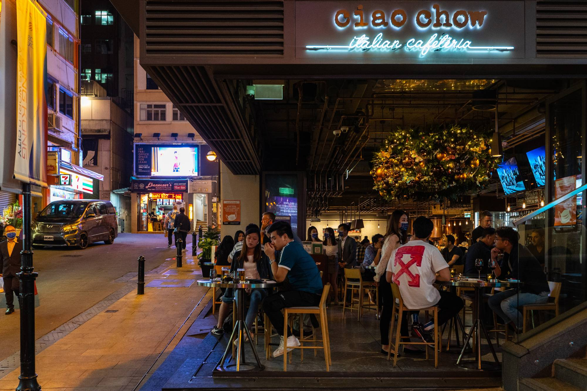 Visitors eat and drink in an open restaurant in the Lan Kwai Fong nightlife area in Hong Kong on Friday.  | BLOOMBERG