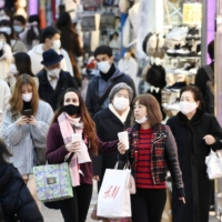 People walk in Tokyo's Harajuku commercial district on Friday amid the coronavirus pandemic. | KYODO