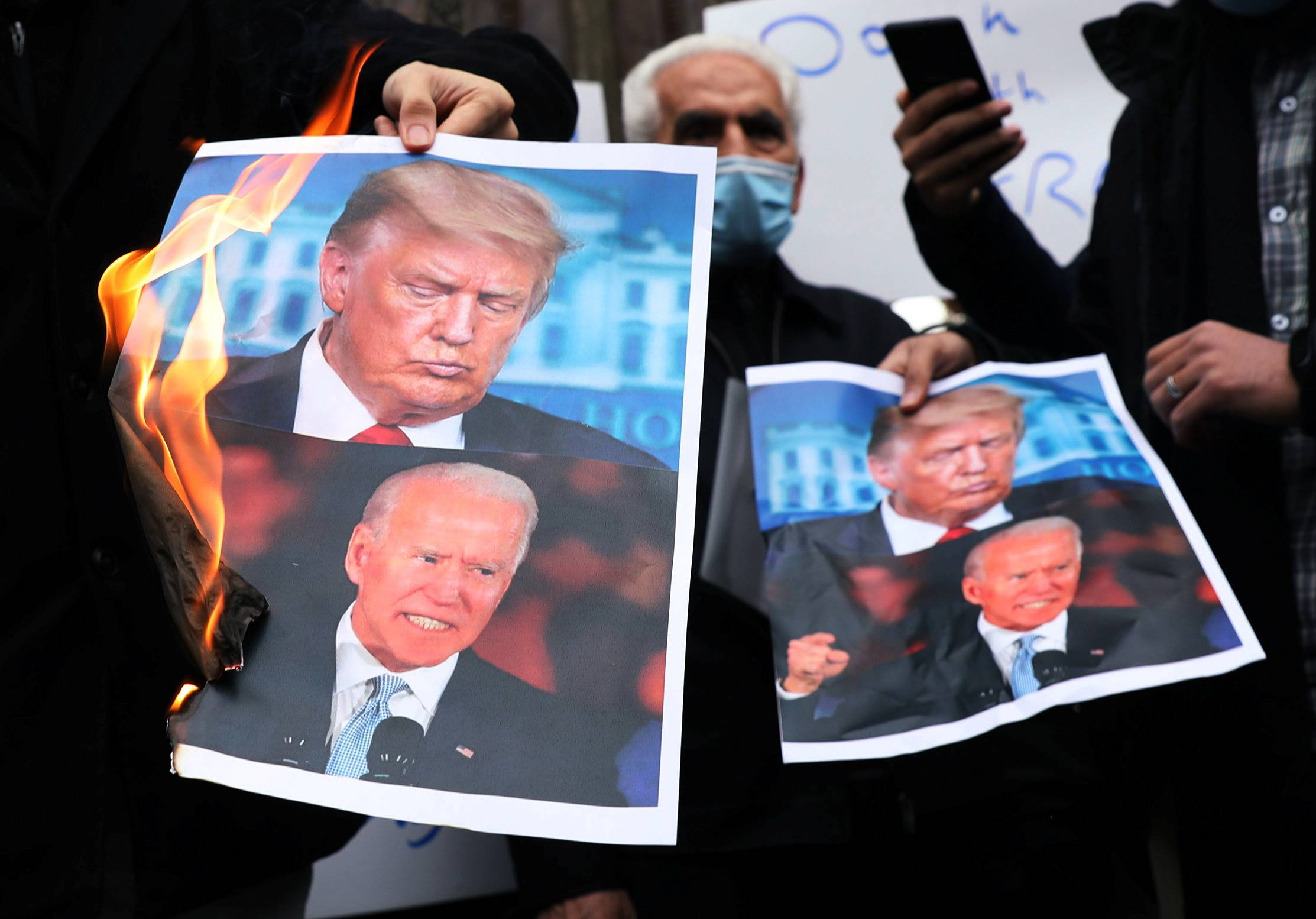 Protesters burn pictures of U.S. President-elect Joe Biden and U.S. President Donald Trump during a demonstration against the killing of Mohsen Fakhrizadeh, Iran's top nuclear scientist, in Tehran on Saturday.  | WEST ASIA NEWS AGENCY / VIA REUTERS