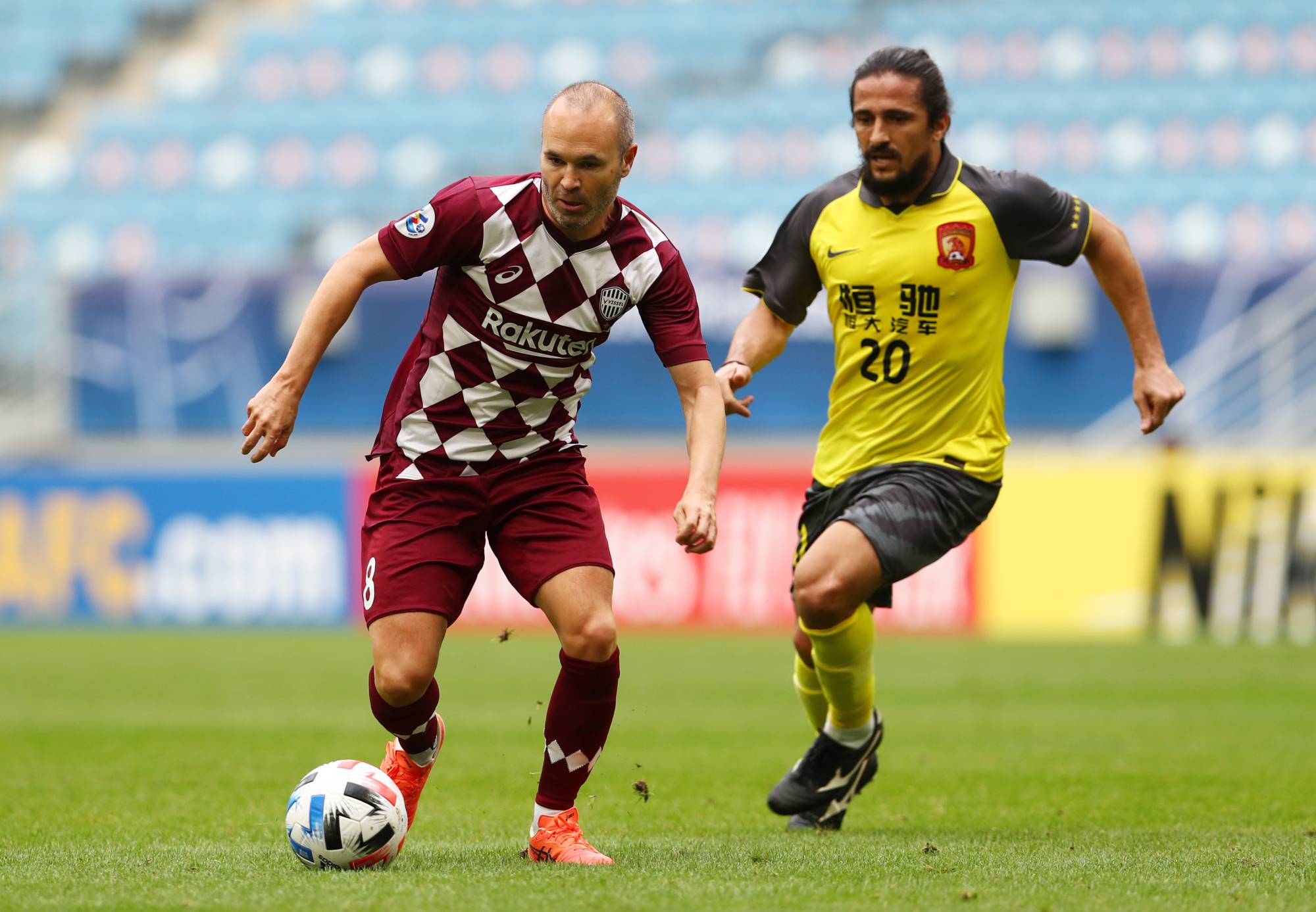 Vissel's Andres Iniesta is pursued by Evergrande's Luo Guofu during an Asian Champions League match on Saturday in Al Wakrah, Qatar. | REUTERS