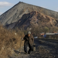 An elderly villager walks along a railway line on the outskirts of Jixi, in Heilongjiang province, China, in October 2015. | REUTERS