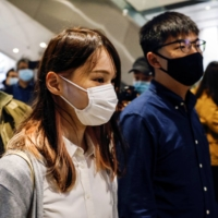 Pro-democracy activists Ivan Lam, Joshua Wong and Agnes Chow arrive at the West Kowloon Magistrates' Courts to face charges related to illegal assembly stemming from 2019, in Hong Kong on Nov. 23. | REUTERS