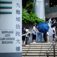 People line up outside the Kowloon City Law Courts Building on May 21 to give support by attending the cases of defendants on trial in relation to last year's protests in Hong Kong. | AFP-JIJI