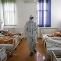 A medical worker treats patients suffering from COVID-19 at Clinical Hospital Center Zemun in Belgrade on Thursday. | REUTERS