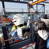 Reporters look at the side of a life-size statue of Gundam set up at Yokohama Pier on Monday. | KYODO