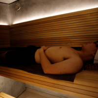 Kotaro Nakahira, a staff member of Solo Sauna Tune, uses its private Finnish-style sauna room during a demonstration. | REUTERS