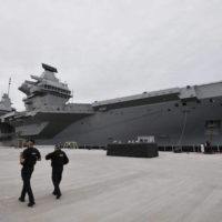 Armed police officers patrol the quayside next to the moored 65,000-ton British aircraft carrier Queen Elizabeth after it arrived at Portsmouth Naval base, its new home port, in Portsmouth, England, on Aug. 16, 2017.  | AFP-JIJI
