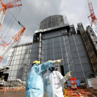A Tepco employee gives a lecture in front of the No. 3 reactor building at Fukushima No. 1 nuclear power plant in 2019. | REUTERS